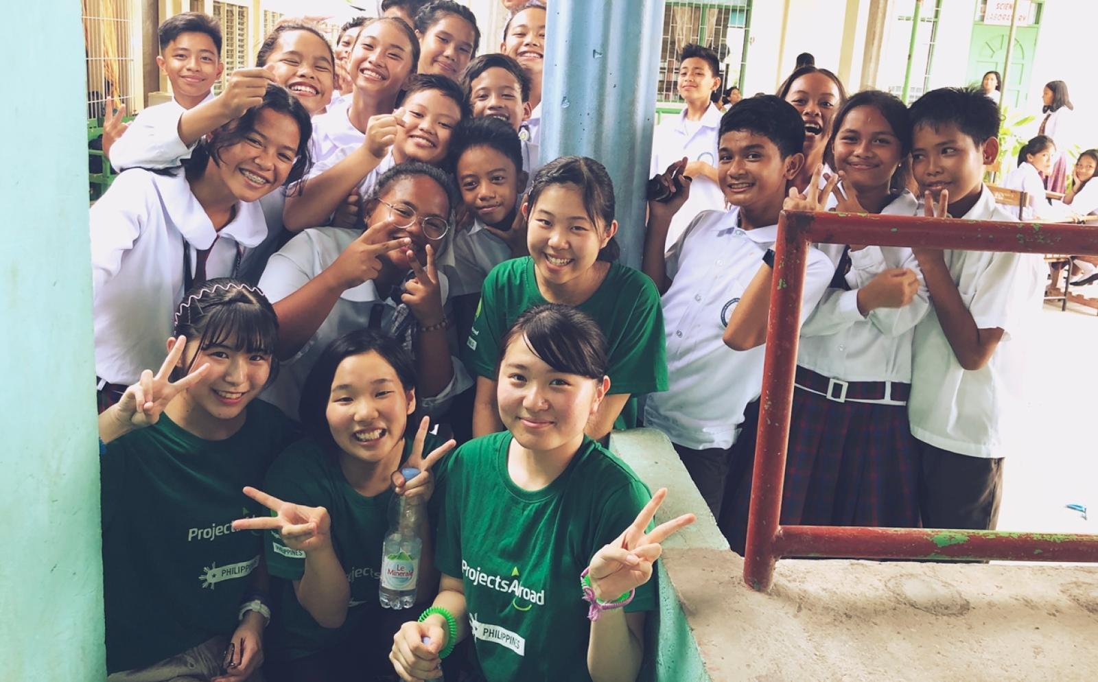 フィリピンの学校で公衆衛生活動に取りむ高校生ボランティア高橋優衣さんと現地の学生